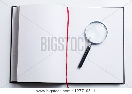 Blank Open Book And Magnifying Glass