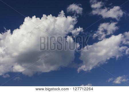 Cumulus clouds against a dark blue sky