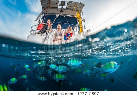 Three girls feed fish from a boat, split shot with underwater view