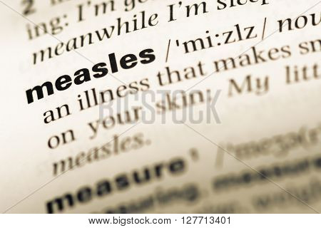 Close Up Of Old English Dictionary Page With Word Measles.