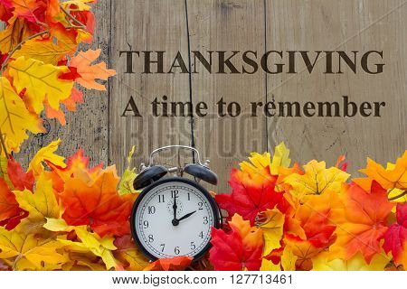 A time to Remember Autumn Leaves and Alarm Clock with grunge wood with text Thanksgiving a time to remember
