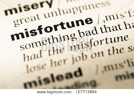Close Up Of Old English Dictionary Page With Word Misfortune.