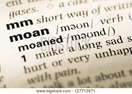 Close Up Of Old English Dictionary Page With Word Moan.