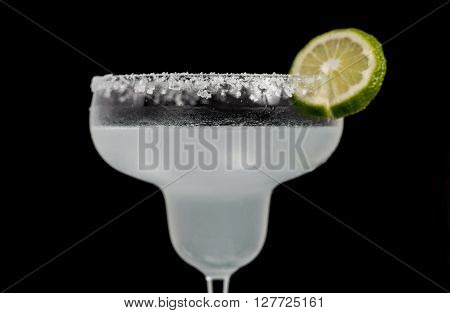 Classic Mexican Cocktail - Margarita in glass with cocktail tubes. Ingredients of cocktail - lime juice, ice, tequila, salt and orange liqueur. Isolated on black bacgkround.