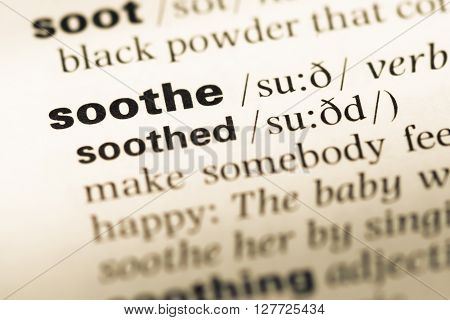Close Up Of Old English Dictionary Page With Word Soothe.