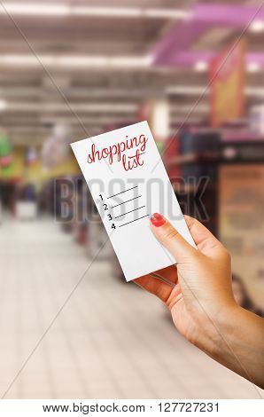 Woman hand holding shopping list in supermarket or hypermarket