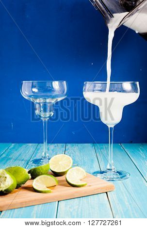 Pouring fresh frozen margarita from cup of blender with orange liquor in fancy margarita glass. Wood background with limes on wood plate