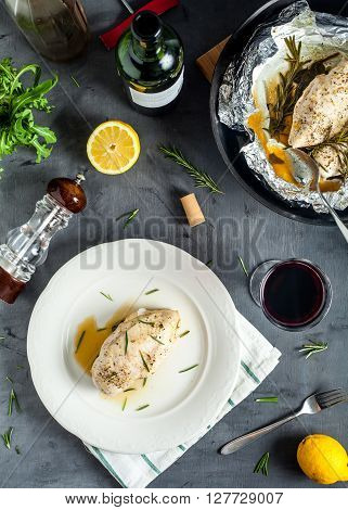 Top view of juicy low fat chicken breast with rosemary steamed in foil on white plate. Near glass of red wine, pepper mill, arugula and pan with chicken. Healthy homemade diet dish on stone background