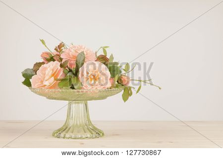Old fashioned pink roses arranged in a green glass vase. Colors muted and vignette added with photographic filter.