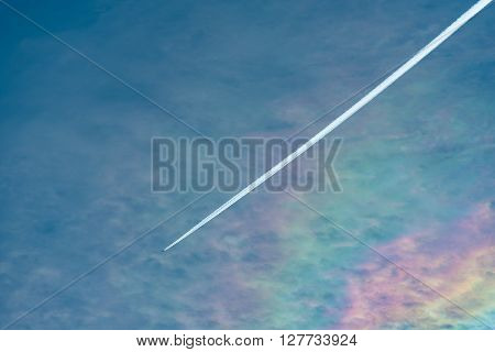 Aircraft at high altitude with condensation trail in blue sky against an unusal flat rainbow.