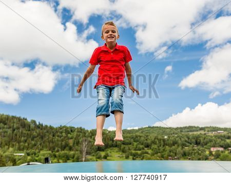 Young Boy Jumping On Trampoline