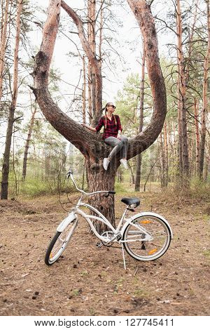Beautiful young hipster girl in a red plaid shirt and leather backpack with a white cruiser bicycle sitting on tree