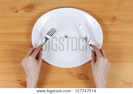 One green pea in plate with skinny hands holding fork and knife