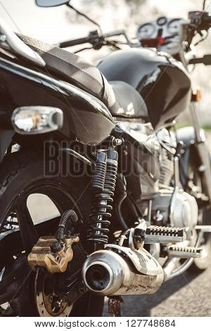 Close up shock absorber, exhaust pipe and disk brake of black shiny motorcycle
