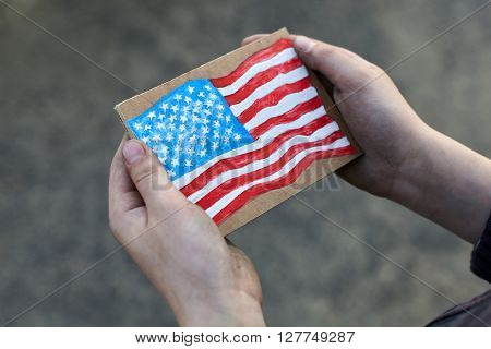 young homeless boy holding a American Flag painted on paper dirty hand