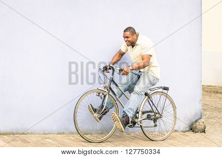 African american guy having fun with vintage bicycle - Free time with young man riding bike in urban city area - Freedom and carefree concept with afroamerican person enjoying everyday life moments