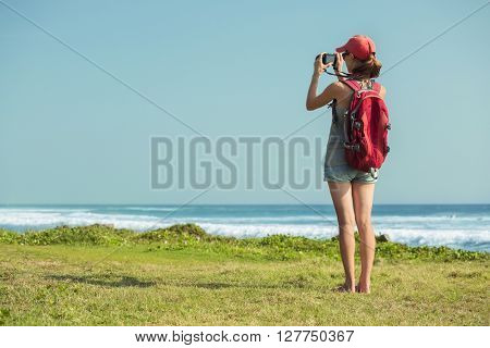 Young lady with rucksack taking a picture of the sea standing on the green glade