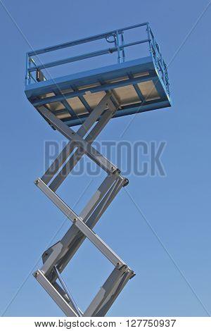 Blue scissor lift platform against clear sky.