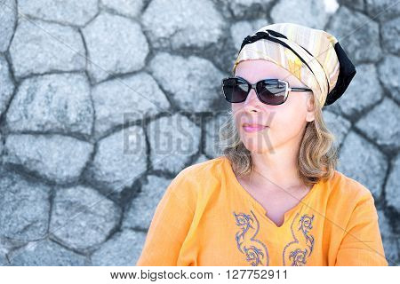 confident natural 50s women posing at stone wall