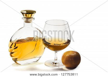 Bottle and a snifter of brandy with a mandarin on a white background