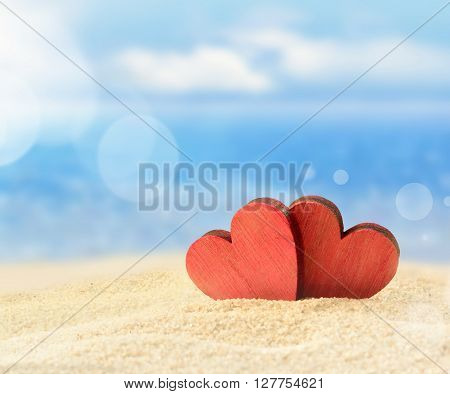 Two red wooden hearts on the summer beach.