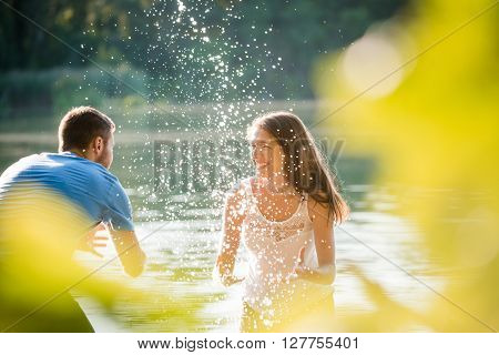 Young couple splashing water on each other on sunny summer day in lake