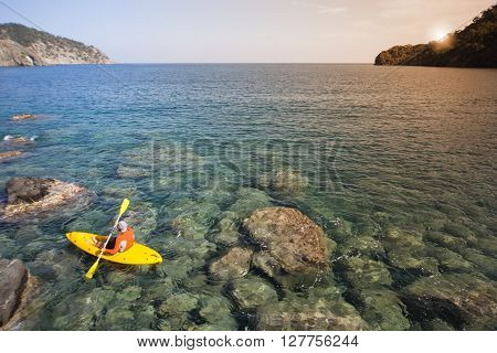 A man traveling by canoe along the coast in the summer.