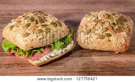 bread with pumpkin seeds stuffed with salami, gorgonzola and salad