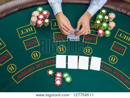 Close up of poker player with playing cards and chips at green casino table, view from above.