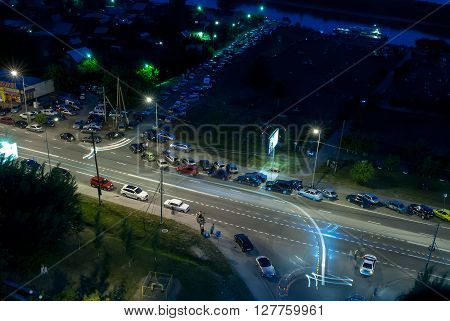 Tyumen, Russia - July 23, 2010: Evening Embankment. Cars along road and patrol of road police returning cars moving to the right. People expect beginning of fireworks festival. Long exposition