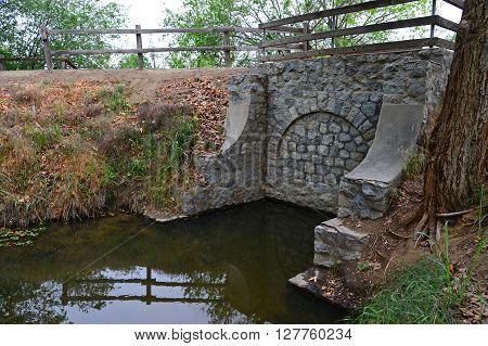 The arch on this old bridge has been walled in, the water flow being directed through an underground pipe.