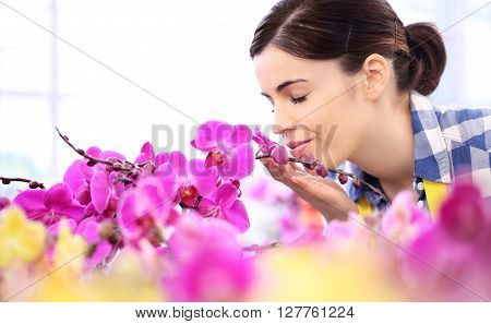 woman in the garden of flowers touches and smells an orchid