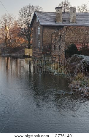 Sunrise landscape with riverbank and red brick old house