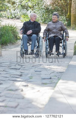 Elderly couple promenading in wheelchairs