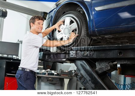 Smiling Mechanic Fixing Alloy To Car Tire
