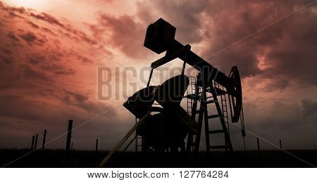 Sunset sky with profiled oil and gas well pump