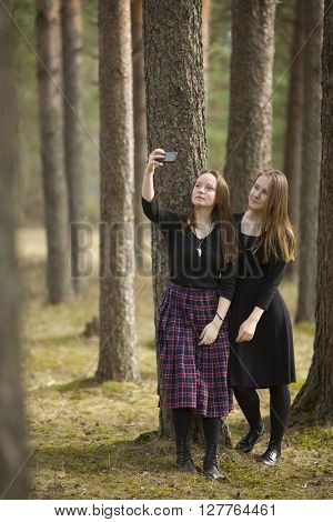 Teenagers girls make selfie phone in the forest.