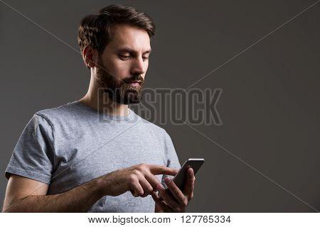 Bearded man using smartphone on dark grey background