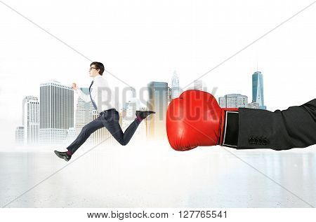 Motivation concept with businessman punching subordinate with boxing glove on New York city background