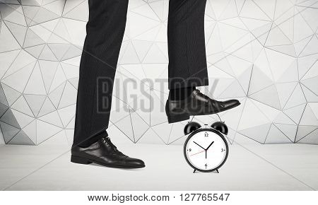 Time reduction concept witt businessman foot stepping on alarm clock. Patterned wall in the background
