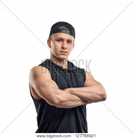 Half-length portrait of muscled young man stands with folded arms. Healthy lifestyle. Fitness and sport. Youth and strength.