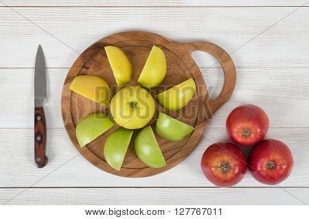 Composition of different color apples on wooden cutting board and knife next to it in top view. Food decoration. Natural source of iron for anemia. Healthy food. Boosting immune system. Table setting. Improving health.