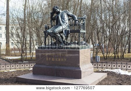 Tsarskoye Selo, Russia -April 16, 2016: Sculpture of a man in a cloak, sitting on a bench, on a high granite pedestal. The monument to Pushkin in Lyceum garden. Sculptor: P.P. Bach. Opened in 1899-1900 gg.