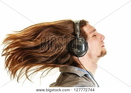 Passionate music lover with long hair flying. Young man listening through headphones relaxing enjyoing. People relax leisure passion concept. Isolated on white background.