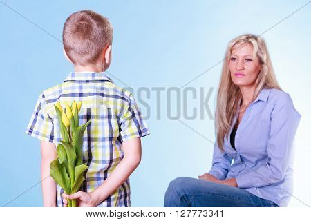 Little Boy With Mother Hold Flowers Behind Back.