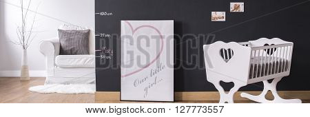 New baby room with cradle and decorative blackboard wall