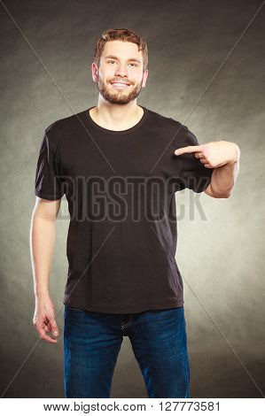 Portrait of happy handsome fashionable casual man in black blank shirt with empty copy space pointing at himself. Young guy in studio on black. Fashion advertisement.