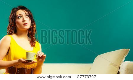Beauty fashion and relax concept. Fashionable girl yellow dress holding hot drink coffee or tea cup sitting on sofa dark green background