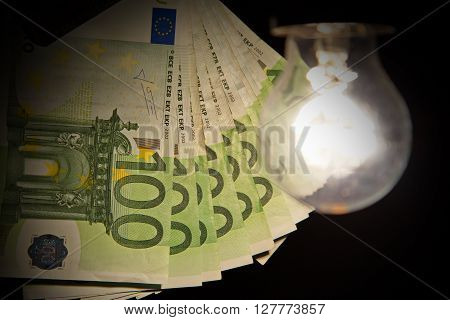 Hanging light bulb dangle on a wire illuminating bank notes