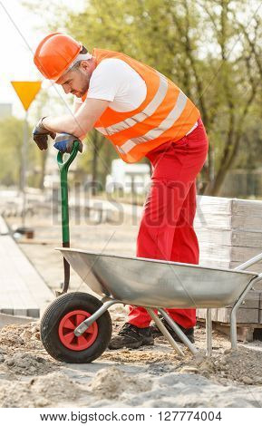 Image of manual worker with shovel and barrow
